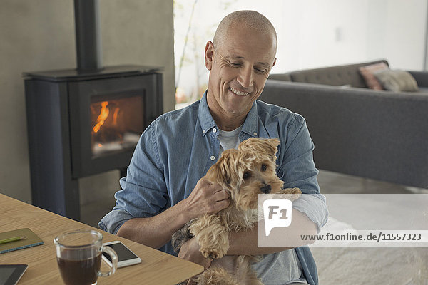 Smiling man petting dog in front of wood stove fireplace