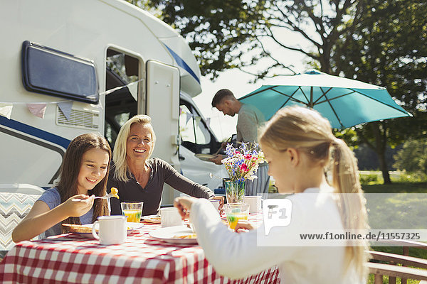 Family enjoying breakfast at table outside sunny motor home