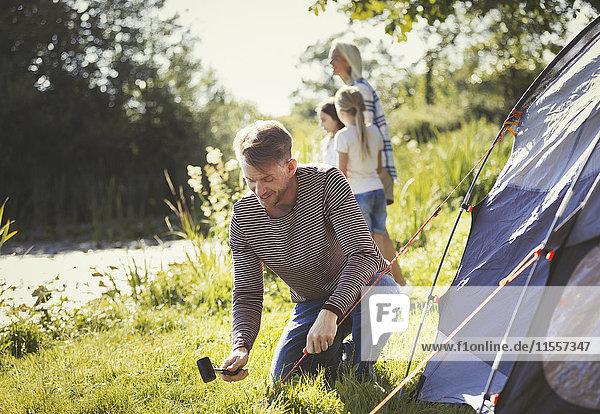 Vater schlägt Zelt auf einem sonnigen Campingplatz am See auf.