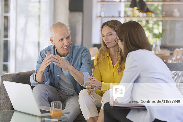 Financial advisor with laptop meeting with couple in living room