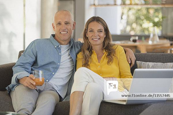 Portrait smiling mature couple using laptop on sofa