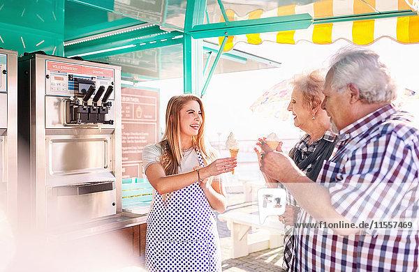 Lächelnde junge Frau serviert Eis für ein älteres Paar außerhalb des Speisewagens.