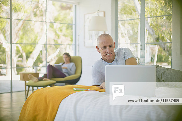 Mature couple relaxing  using laptop and digital tablet in bedroom
