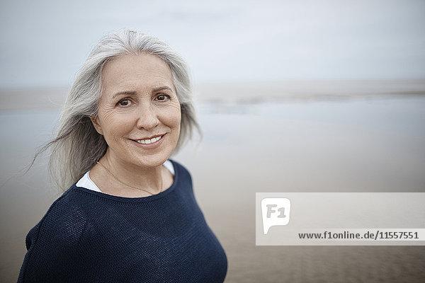 Portrait lächelnde Seniorin am Strand