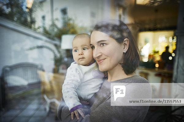 Lächelnde Mutter hält Baby-Tochter am Fenster