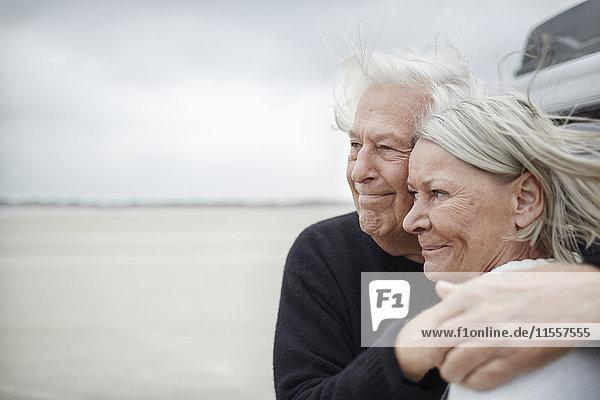 Zärtliches Seniorenpaar  das sich am Strand umarmt und wegschaut.