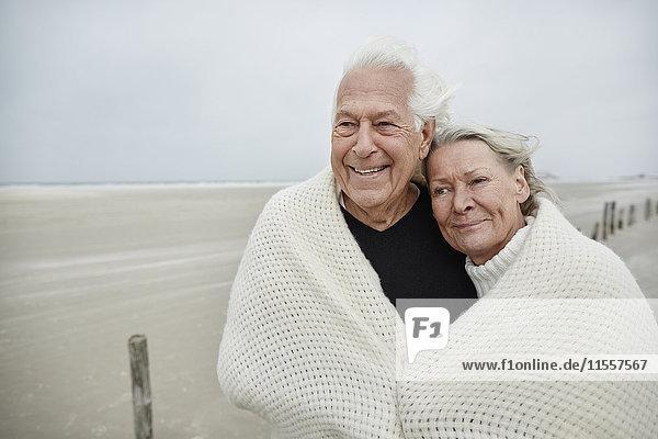 Lächelndes  liebevolles Seniorenpaar in eine Decke am Strand gewickelt