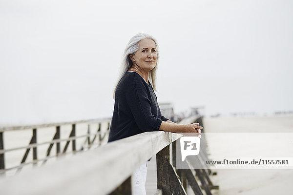 Porträt selbstbewusste Seniorin am Strandpromenadengeländer