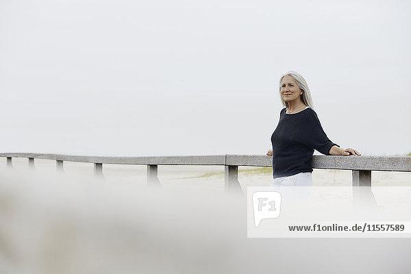 Selbstbewusste Seniorin  die sich an der Strandpromenade lehnt.