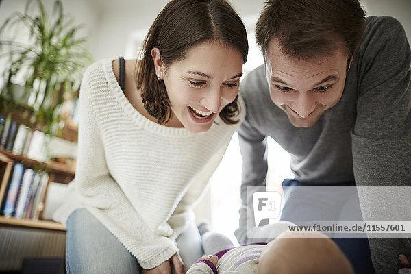 Verspielte Eltern schauen auf die kleine Tochter herab