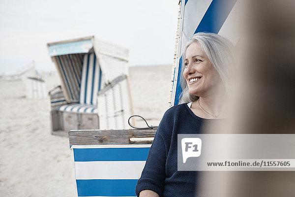 Lächelnde Seniorin schaut weg am Strand