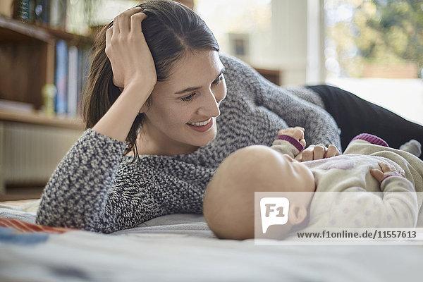 Lächelnde Mutter schaut auf die kleine Tochter