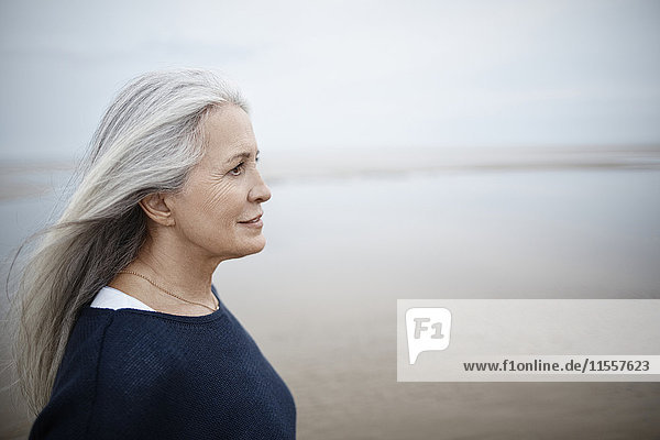 Nachdenkliche Seniorin mit Blick auf den Winterstrand