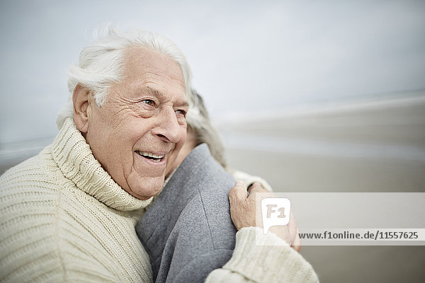 Liebevolles Seniorenpaar beim Umarmen am Winterstrand
