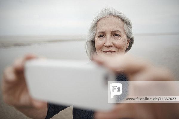 Seniorin nimmt Selfie mit Fotohandy am Winterstrand mit.