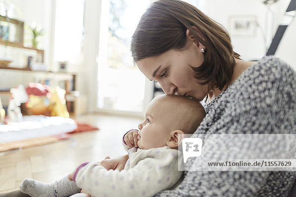 Mutter küsst kleine Tochter auf den Kopf