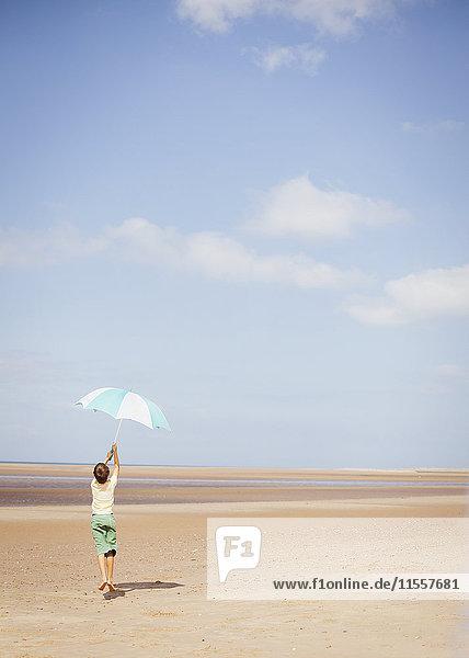 Boy holding striped umbrella overhead on sunny summer beach below blue sky Boy holding striped umbrella overhead on sunny summer beach below blue sky