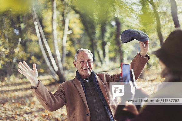 Senior Mann posiert für Frau mit Fotohandy im Herbstpark