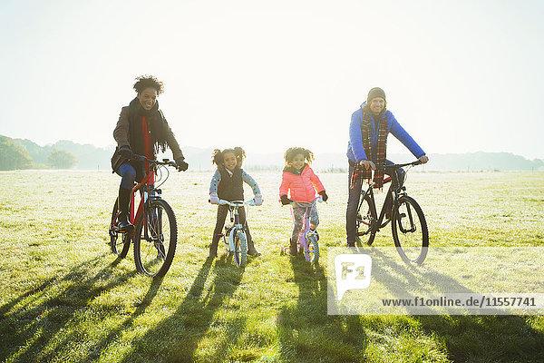 Portrait junges Familienradfahren im sonnigen Herbstparkgras