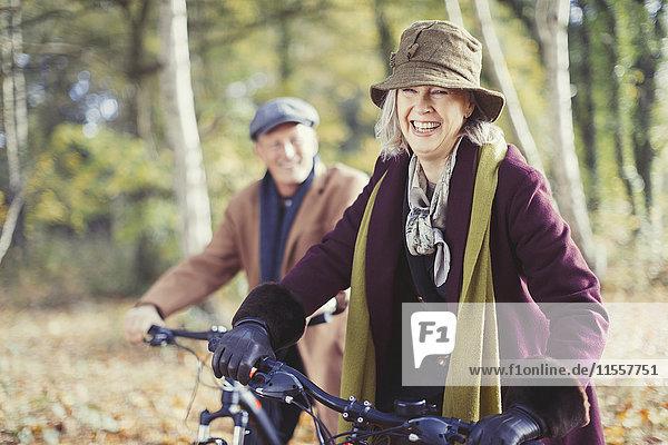 Lächelndes Seniorenpaar Radfahren im sonnigen Herbstwald