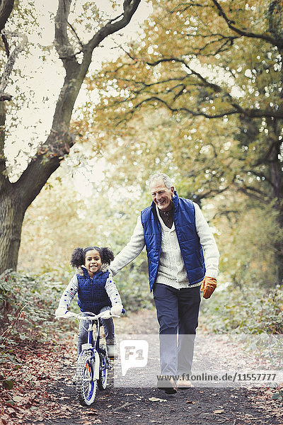 Großvater und Enkelin Radfahren auf dem Weg im Herbstpark