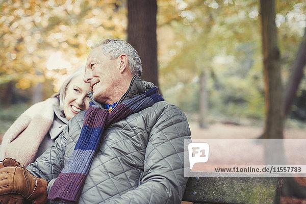Liebevolles Seniorenpaar auf der Bank im Herbstpark