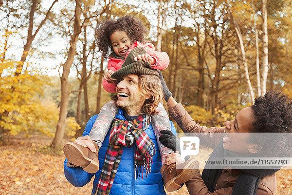 Verspielte junge Familie im Herbstpark