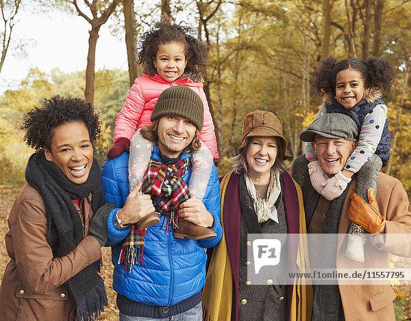 Portrait lächelnde Mehrgenerationen-Familie im Herbstwald