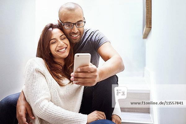Lächelndes Paar mit Fotohandy  das Selfie auf der Treppe nimmt.