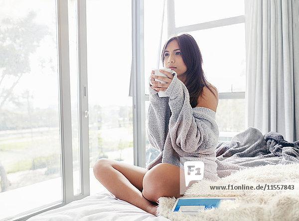 Gelassene Frau trinkt Kaffee auf dem Bett