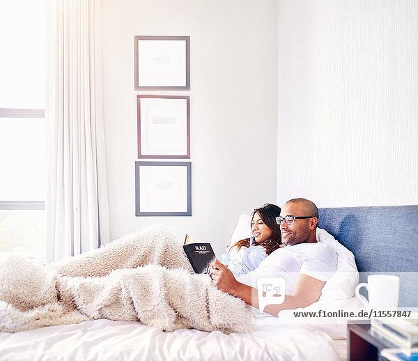 Lächelndes Paar entspannt  Lesebuch im Bett