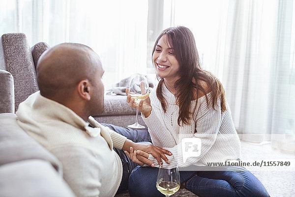Lächelndes Paar trinkt Weißwein im Wohnzimmer
