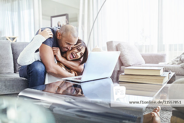 Verspieltes Pärchen beim Umarmen und Benutzen des Laptops im Wohnzimmer