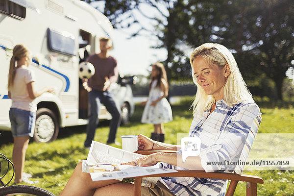 Lächelnde Frau liest Magazin und trinkt Kaffee vor dem sonnigen Wohnmobil