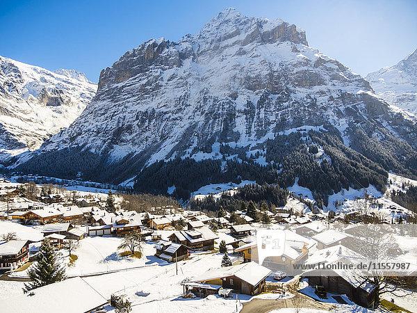 Schweiz  Kanton Bern  Grindelwald  Stadtbild im Winter bei Sonnenaufgang mit Mittelhorn