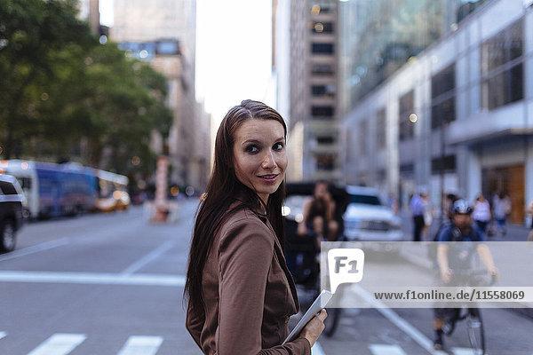 USA  New York  Manhattan  Portrait einer jungen Geschäftsfrau mit Tablette über die Straße
