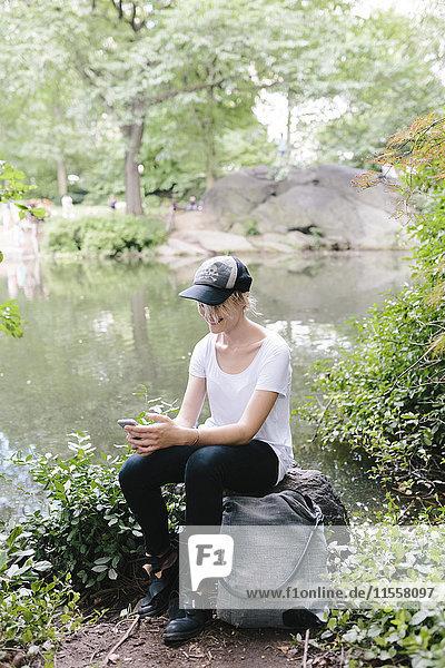 Junge Frau am Seeufer im Park mit Blick auf das Handy