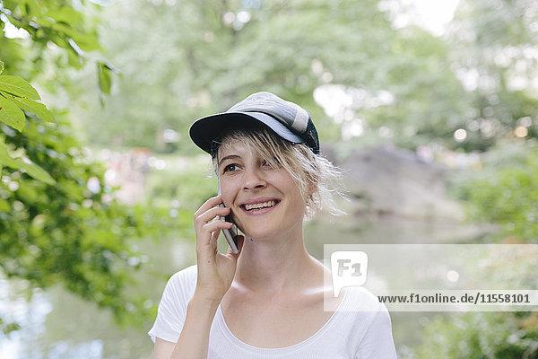 Lächelnde junge Frau im Park spricht am Handy