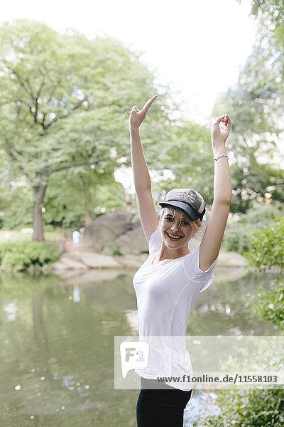Porträt einer glücklichen jungen Frau am Seeufer im Park