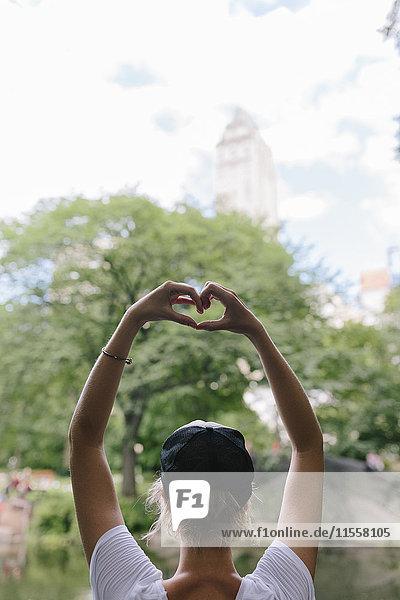 Rückansicht einer jungen Frau am Seeufer im Park  die mit ihren Händen ein Herz formt.
