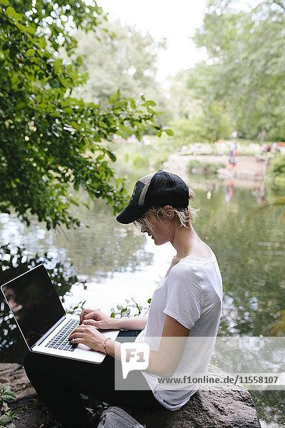 Junge Frau sitzt am Seeufer im Park mit Laptop