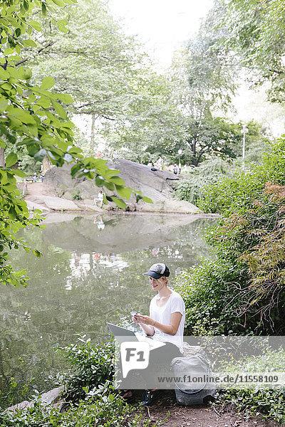 Junge Frau sitzt am Seeufer im Park mit Handy und Laptop