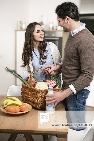 Junges Paar beim Auspacken auf dem Küchentisch