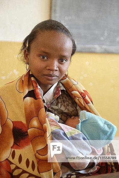 Madagaskar  Fianarantsoa  Junge Mutter mit Baby im Arm