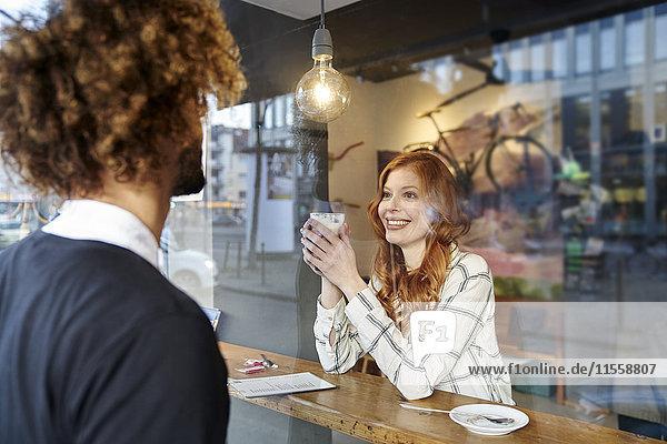 Mann schaut lächelnde junge Frau in einem Café an