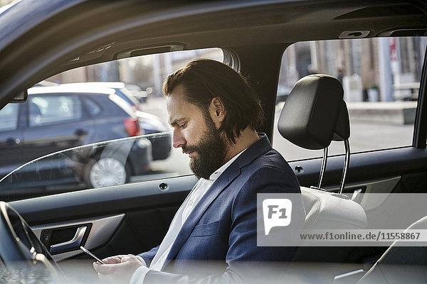 Geschäftsmann mit Handy im Auto