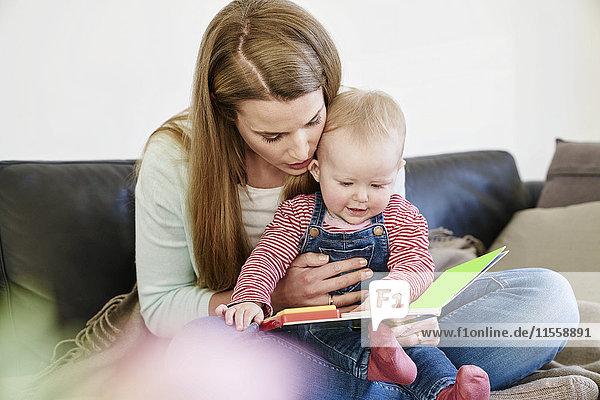 Mutter und kleines Mädchen zu Hause beim Betrachten des Buches