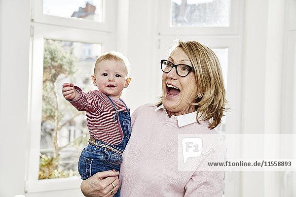 Fröhliche Großmutter trägt ein kleines Mädchen zu Hause