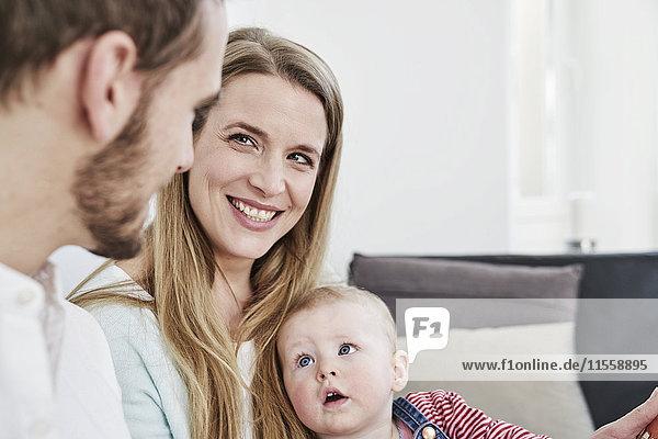 Lächelnde Mutter mit Vater und Tochter zu Hause