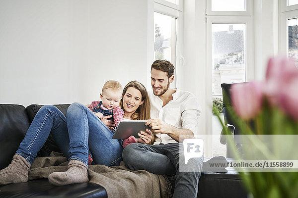 Eltern mit Baby-Mädchen beim Betrachten der Tablette auf der Couch